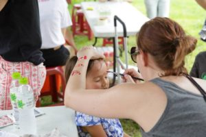 Celebration Canada volunteers at the face-painting booth in the Kids Zone.